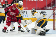 Nashville Predators goaltender Pekka Rinne (35) stops the puck as Detroit Red Wings center Dylan Larkin (71) tries to play the rebound as Ben Harpur (17) defends in the second period of an NHL hockey game Thursday, Feb. 25, 2021, in Detroit. (AP Photo/Paul Sancya)