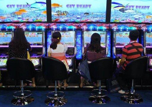 Visitors play a game during the G2E Asia gaming expo in Macau on May 23. As billions of dollars pour into Asia's gleaming casinos, they are becoming the front line of a sometimes hugely lucrative battle between cheats and the house, say experts
