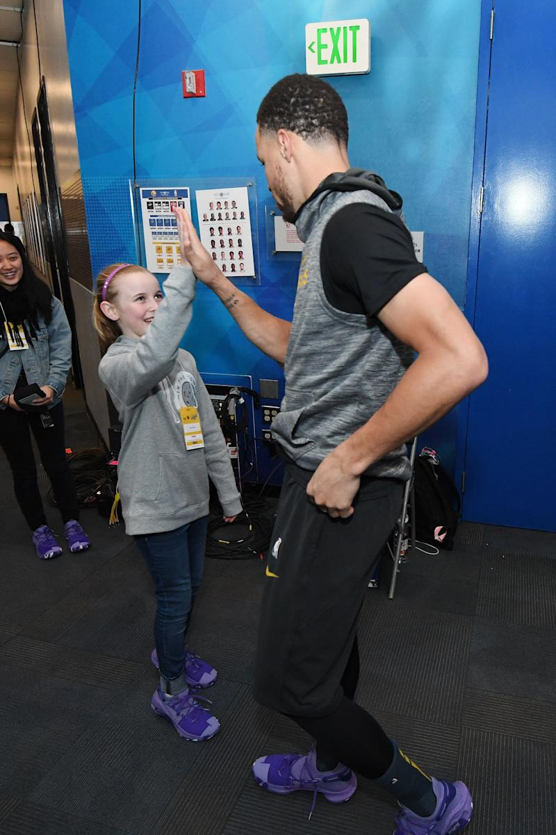 OAKLAND, CA - MARCH 8: Riley Morrison high fives Stephen Curry #30 of the Golden State Warriors prior to the game against the Denver Nuggets on March 8, 2019 at ORACLE Arena in Oakland, California. NOTE TO USER: User expressly acknowledges and agrees that, by downloading and or using this photograph, user is consenting to the terms and conditions of Getty Images License Agreement. Mandatory Copyright Notice: Copyright 2019 NBAE (Photo by Noah Graham/NBAE via Getty Images)