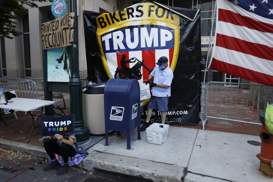 A postal worker collects mail from a mailbox inside the protest pen, as a handful of supporters of President Donald Trump continue to demonstrate, outside the Pennsylvania Convention Center in Philadelphia, Tuesday, Nov. 10, 2020. (AP Photo/Rebecca Blackwell)