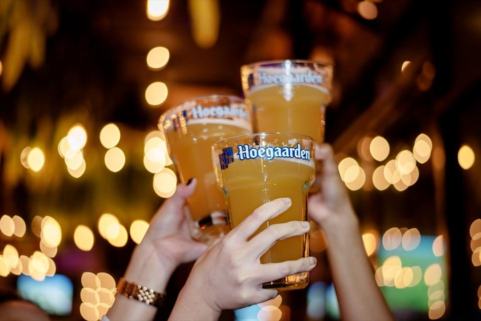Hoegaarden beer cups in the air for a cheers