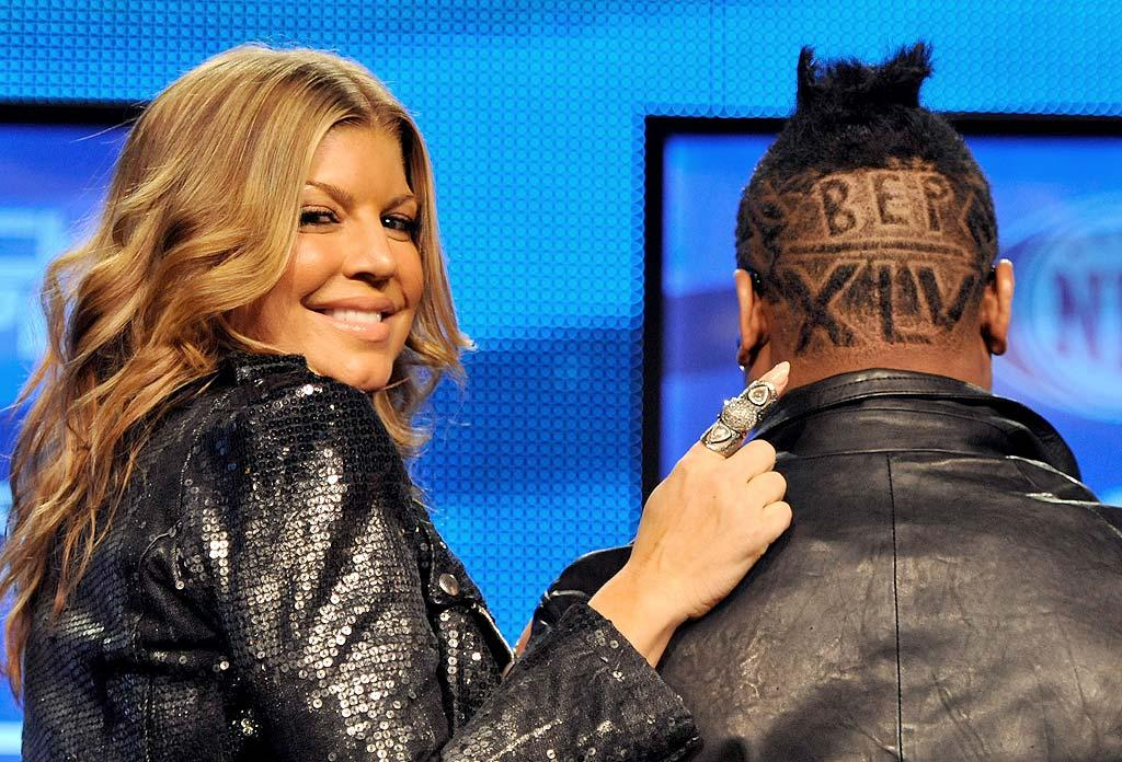 """Fergie cheekily pointed out her Black Eyed Peas band mate apl.de.ap's new 'do in honor of Super Bowl XLV at a press conference Dallas, Texas, Thursday. The best-selling band will be playing during the half-time show on the big day. Will you be cheering for the Green Bay Packers or the Pittsburgh Steelers on Sunday? Kevin Mazur/<a href=""""http://www.wireimage.com"""" target=""""new"""">WireImage.com</a> - February 3, 2011"""