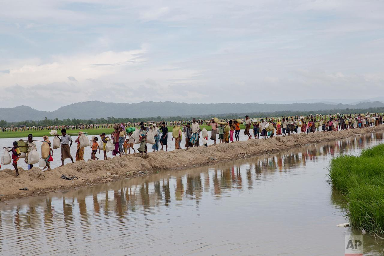 <p>Rohingya Muslims, who spent four days in the open after crossing over from Myanmar into Bangladesh, carry their children and belongings after they were allowed to proceed towards a refugee camp at Palong Khali, Bangladesh. More than 580,000 refugees have arrived in Bangladesh since 25 August, when Myanmar security forces began a scorched-earth campaign against Rohingya villages. Myanmar's government has said it was responding to attacks by Muslim insurgents, but the United Nations and others have said the response was disproportionate. (AP Photo/Dar Yasin) </p>