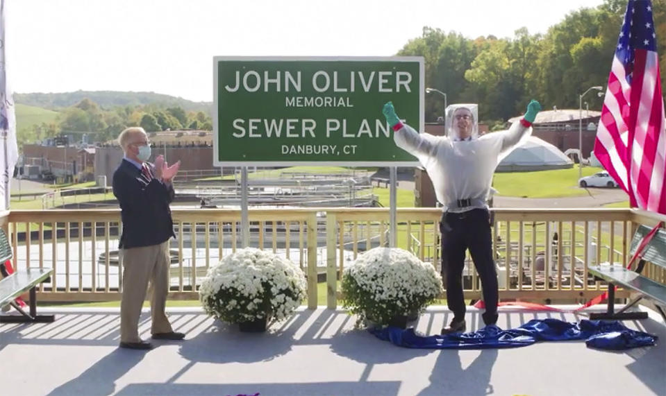 """This image taken from video released by HBO shows John Oliver, host of """"Last Week Tonight with John Oliver,"""" right, with Mayor Mark Boughton during a dedication ceremony for The John Oliver Memorial Sewer Plant, in Danbury, Conn. Oliver made a secret trip to Connecticut last week to help cut the ribbon on a sign naming a sewage treatment plant in his honor. (HBO via AP)"""
