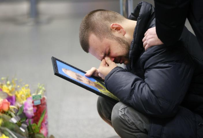 FILE - In this Jan. 10, 2020 file photo, the partner of Julia Sologub, a member of the flight crew of the Ukrainian 737-800 plane that crashed on the outskirts of Tehran, reacts as he holds a portrait of her at a memorial inside Borispil international airport outside in Kyiv, Ukraine. Iran's cabinet has created a compensation fund to pay the families of the 176 victims of the Ukrainian passenger plane that was shot down by Iranian forces outside Tehran last January, the president announced Wednesday, Dec. 30. (AP Photo/Efrem Lukatsky, File)