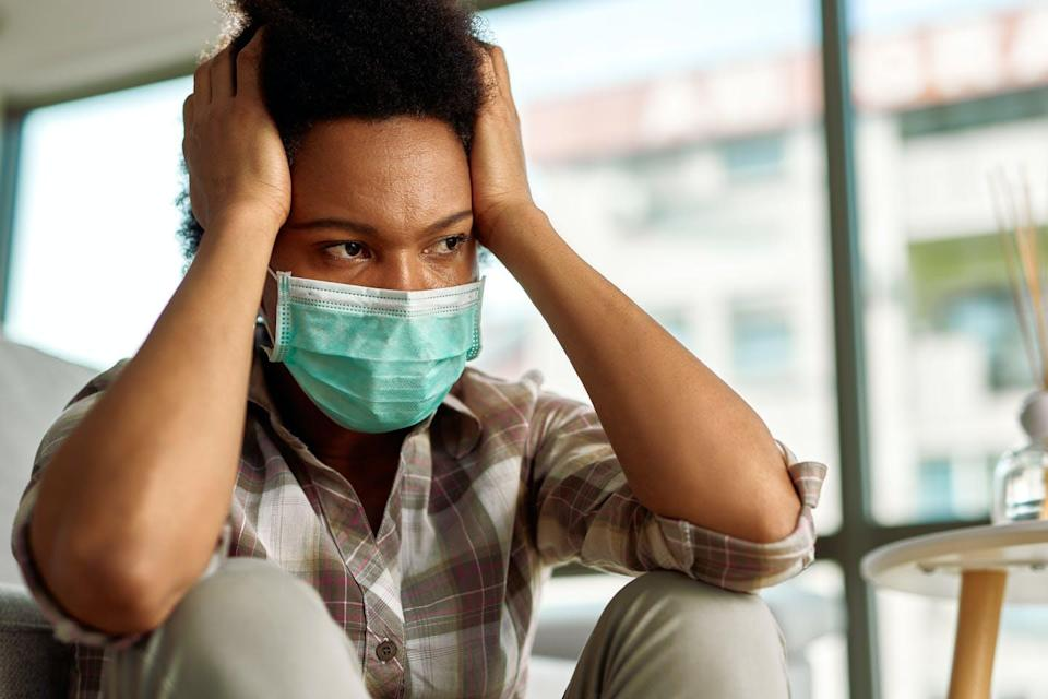 A man wearing a surgical mask with his hands on either side of his head.