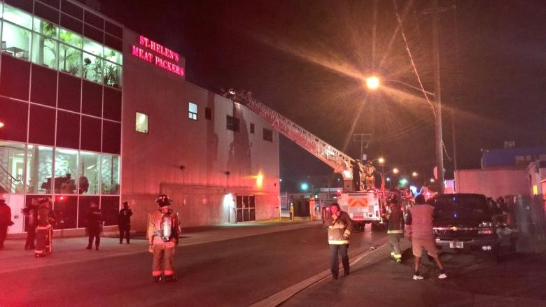 Health officials inspecting products at meat packaging plant after rooftop fire