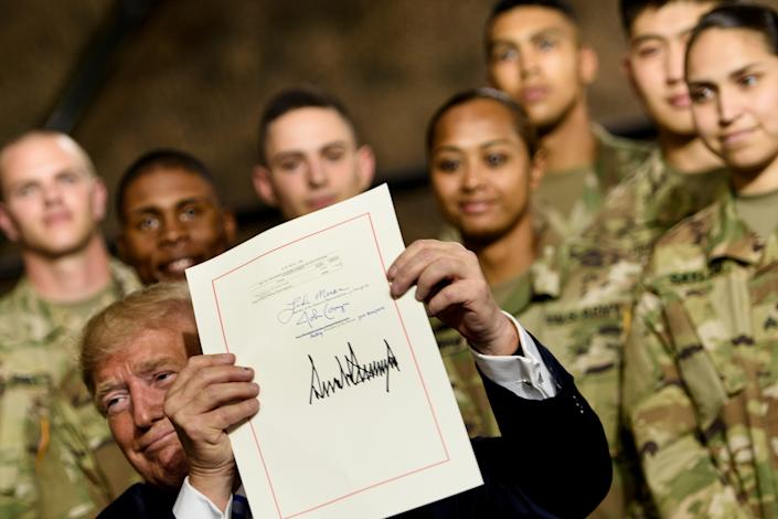 US President Donald Trump holds the John S. McCain National Defense Authorization Act for Fiscal Year 2019 after signing it at Fort Drum, New York, on August 13, 2018. (Brendan Smialowski/AFP via Getty Images)