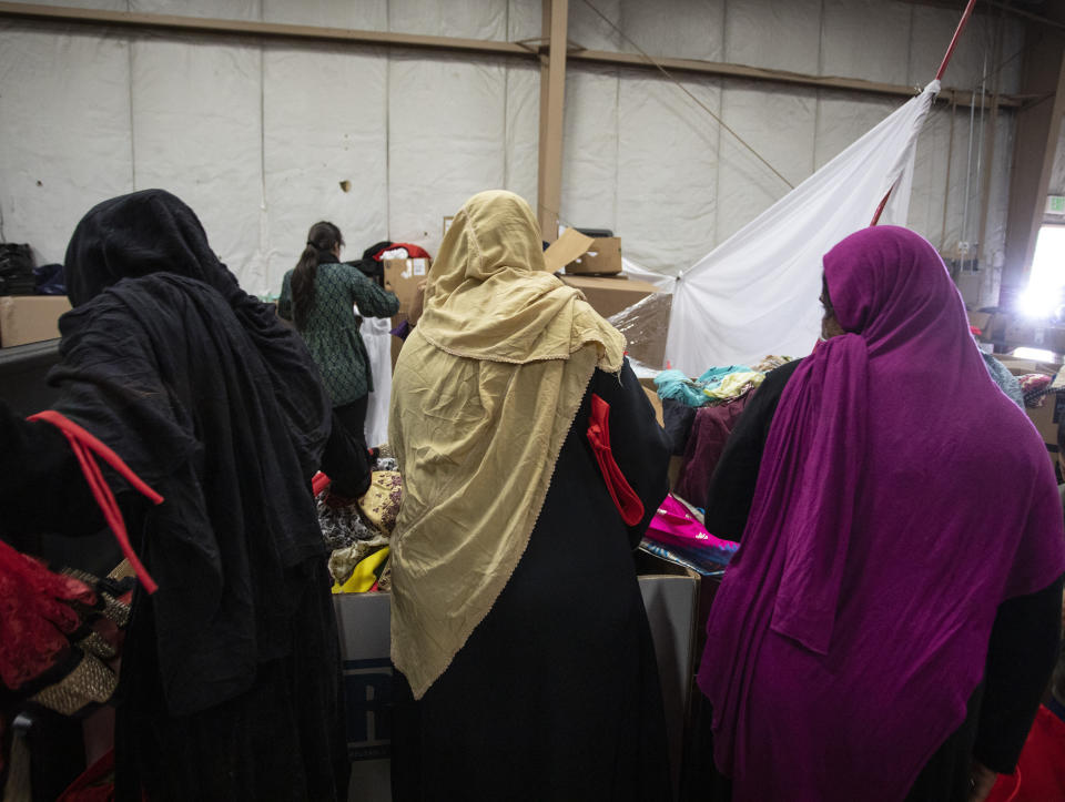 Afghan refugees look for donated clothing and shoes at the donation center at the Fort McCoy U.S. Army base on Thursday, Sept. 30, 2021, in Fort McCoy, Wis. The fort is one of eight military installations across the country that are temporarily housing the tens of thousands of Afghans who were forced to flee their homeland in August after the U.S. withdrew its forces from Afghanistan and the Taliban took control. (Barbara Davidson/Pool Photo via AP)