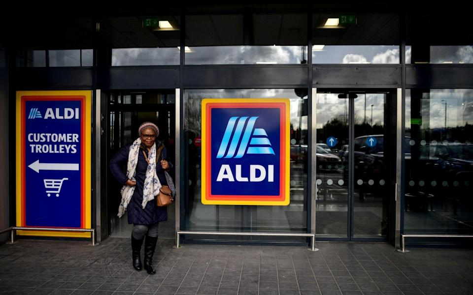 A shopper leaves an Aldi store in London - Peter Summers/REUTERS