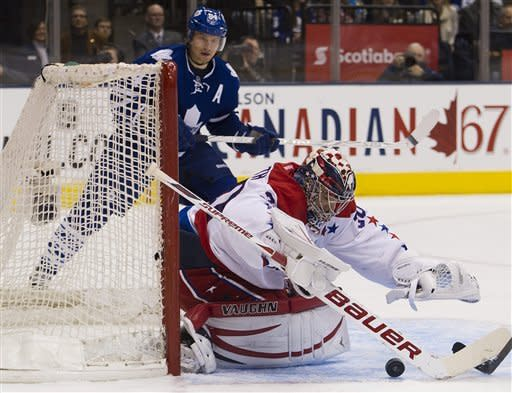 Washington Capitals goalie Michal Neuvirth, right, covers a loose puck as Toronto Maple Leafs' Mikhail Grabovski, back, looks on during second-period NHL hockey game action in Toronto, Saturday, Feb. 25, 2012. (AP Photo/The Canadian Press, Nathan Denette)