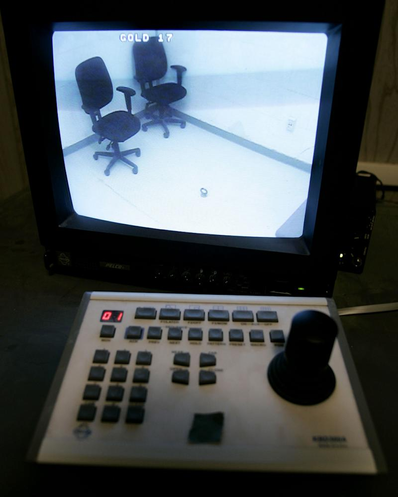 A control panel used by analysts is shown as an interrogation room is displayed on a closed circuit television where detainees are interviewed at Camp Delta at the U.S. Naval Base Guantanamo Bay, Cuba, July 28, 2004. On the floor in the room is an eye bolt where detainees can be chained, if needed. Preparations are nearing completion on the Naval base for war crimes tribunals, the first held by the United States since the World War II era. The proceedings are expected to begin within months. U.S. military censors reviewed photographs from inside the prison. Joe Skipper/Reuters
