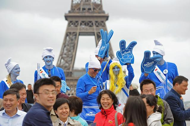 PARIS, FRANCE - JUNE 22: A group of tourists mixes with Smurf Ambassadors as they pose for a group photo on the Trocadero plaza as part of Global Smurfs Day celebrations on June 22, 2013 in Paris, France. The Eiffel tower is seen behind. (Photo by Pascal Le Segretain/Getty Images for Sony Pictures Entertainment)