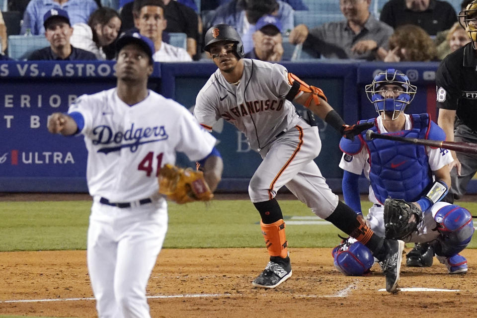San Francisco Giants' Thairo Estrada, center, runs to first after hitting a solo home run as Los Angeles Dodgers relief pitcher Josiah Gray, left, watches along with catcher Austin Barnes during the fifth inning of a baseball game Tuesday, July 20, 2021, in Los Angeles. (AP Photo/Mark J. Terrill)