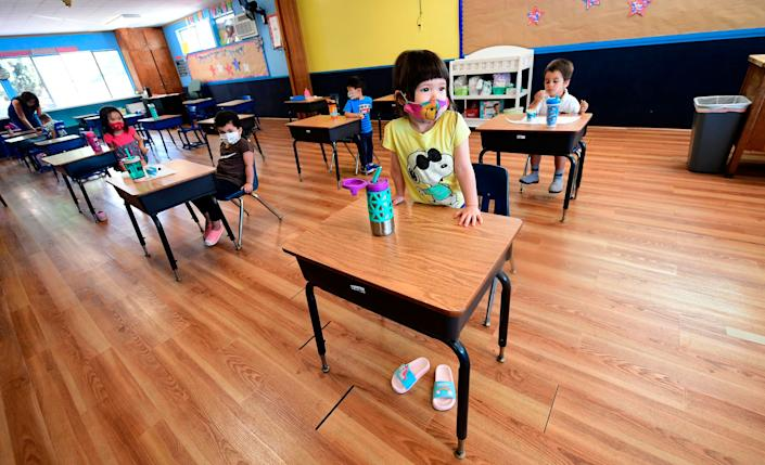 Children in a preschool class wear masks and sit at desks spaced apart as per coronavirus guidelines during summer school sessions in Monterey Park, California, on July 9.