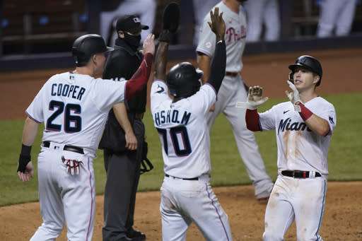 Miami Marlins' Garrett Cooper (26), Jazz Chisholm (70) and Corey Dickerson, right, celebrate after they scored on a double by Starling Marte during the eighth inning of a baseball game against the Philadelphia Phillies, Thursday, Sept. 10, 2020, in Miami. (AP Photo/Wilfredo Lee)