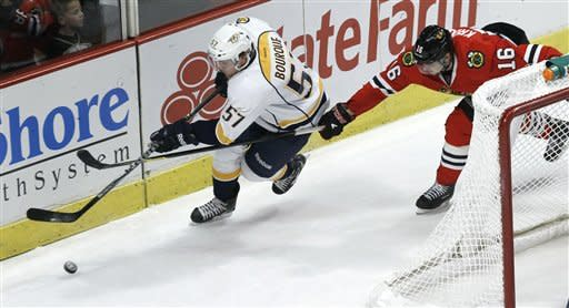 Nashville Predators left wing Gabriel Bourque (57) controls the puck behind the Chicago Blackhawks' net as center Marcus Kruger chases during the second period of an NHL hockey game Tuesday, Jan. 24, 2012, in Chicago. (AP Photo/Charles Rex Arbogast)