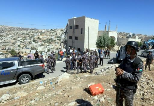 Jordanian security forces gather near a partially collapsed building in the town of Salt northwest of Amman a day after a deadly raid targeting militants