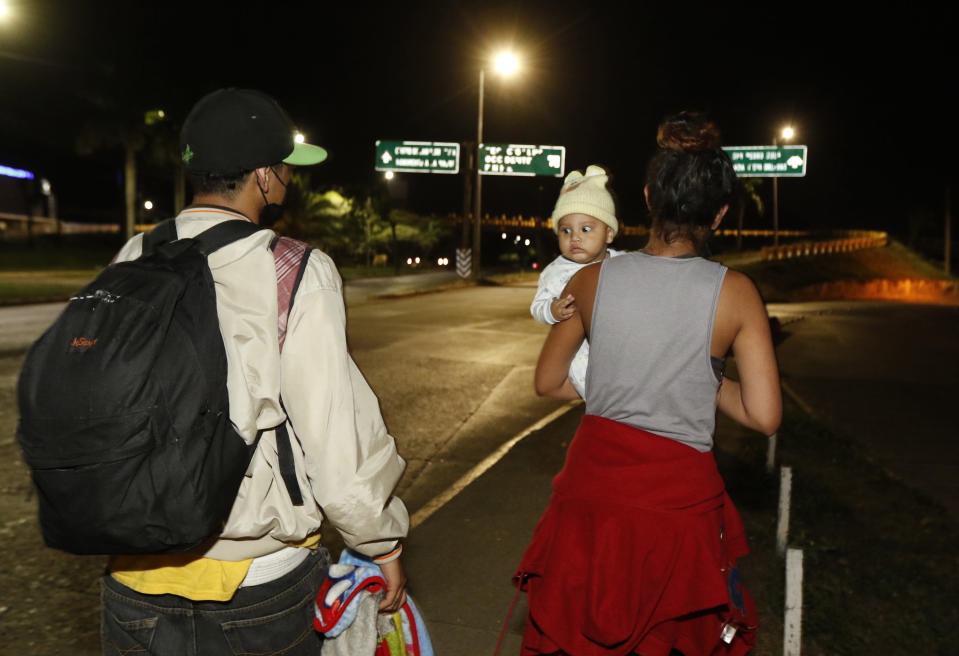 Migrants who aim to reach the U.S. walk with a bigger group along a highway as they leave San Pedro Sula, Honduras before dawn Tuesday, March 30, 2021. (AP Photo/Delmer Martinez)
