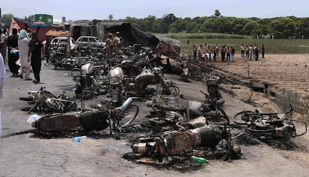 <p>Pakistan army soldiers stands guard while rescue workers examine the site of an oil tanker explosion at a highway near Bahawalpur, Pakistan, Sunday, June 25, 2017. An overturned oil tanker burst into flames in Pakistan on Sunday, killing more than one hundred people who had rushed to the scene of the highway accident to gather leaking fuel, an official said. (AP Photo/Iram Asim) </p>