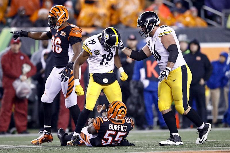 JuJu Smith-Schuster of the Pittsburgh Steelers stands over Vontaze Burfict of the Cincinnati Bengals after a hit during the second half at Paul Brown Stadium on December 4, 2017