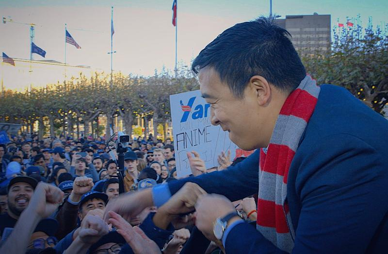 Andrew Yang fist-bumps supporters at a recent rally in San Francisco. The presidential hopeful says his focus on economic issues cuts across ethnic divisions.
