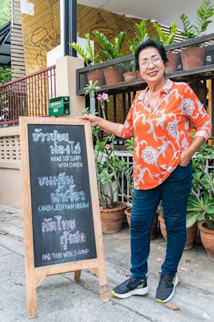 Siripha 'Lek' Chariton poses with a sign in front of her restaurant.