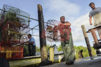 Commercial crabbers Derek Grose, right, Joe Becker, center, and Patrick Nata collect crab traps before the flood wall closes as Hurricane Ida approaches the Louisiana coast in St. Bernard, La. Saturday, Aug. 28, 2021. Residents across Louisiana's coast rushed to prepare for the approach of an intensifying Hurricane Ida. The storm is expected to bring winds as high as 140 mph when it slams ashore late Sunday.( Max Becherer, NOLA.com, The Times-Picayune/The New Orleans Advocate via AP)