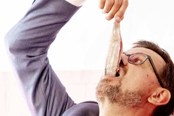 THE HAGUE, NETHERLANDS - JUNE 15: GGD chairman Andre Rouvoet eats fish from the first barrel of new herring on June 15, 2021 in The Hague, Netherlands. The traditional first barrel is presented to the national health services GGD. Chairman André Rouvoet is offered the so-called Hollandse Nieuwe (New Dutch) at a vaccination location in The Hague by the Dutch Fish Marketing Board. (Photo by Niels Wenstedt/BSR Agency/Getty Images)