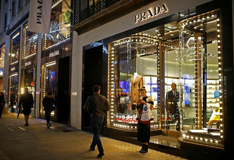 Festive lights decorate the Prada store on New Bond Street as shoppers do Christmas shopping in central London
