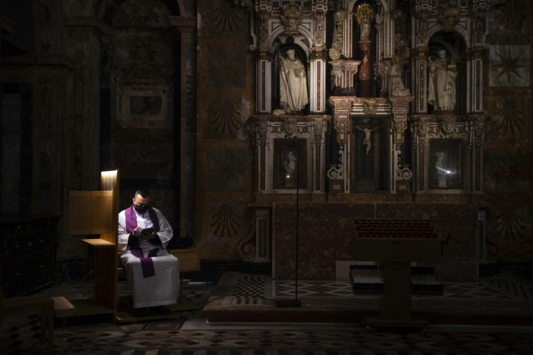 A Spanish priest presides over an empty cathedral as virus cases worldwide topped 100 million
