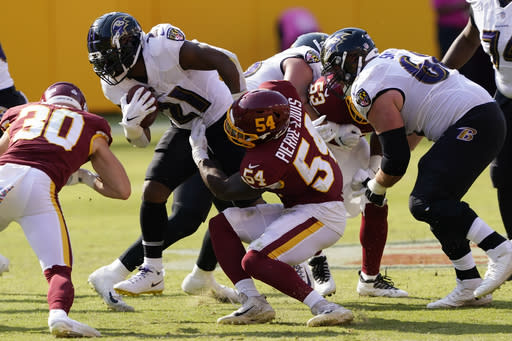 Baltimore Ravens running back Mark Ingram (21) is hit by Washington Football Team outside linebacker Kevin Pierre-Louis (54) during the second half of an NFL football game, Sunday, Oct. 4, 2020, in Landover, Md. (AP Photo/Susan Walsh)