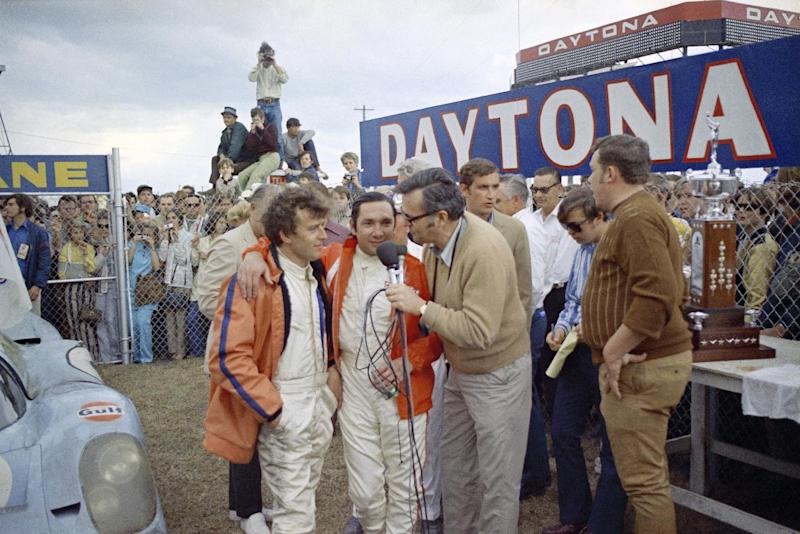 FILE - In this Jan. 31, 1971, file photo, winning co-drivers Jackie Oliver, left, of England, and Pedro Rodriguez, of Mexico, are interviewed by broadcaster Chris Economaki after the 24 Hours of Daytona sports-car race at Daytona Speedway in Daytona Beach, Fla., on Jan. 31, 1971. Economaki, a journalist regarded as the authoritative voice in motorsports for decades, died Friday, Sept. 28, 2012. He was 91. National Speed Sport News, where Economaki worked as an editor for more than 60 years, announced his death Friday. It did not release a cause of death. (AP Photo/Gene Blythe, File)