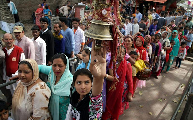 An Indian Hindu devotee rings the bell as a ritual as she stands with other devotees in a queue to pray - Credit: EPA