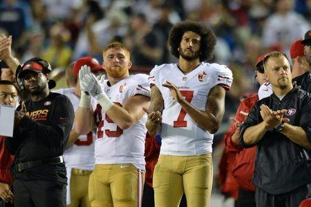 FILE PHOTO - Sep 1, 2016; San Diego, CA, USA;  San Francisco 49ers quarterback Colin Kaepernick (7) and fullback Bruce Miller (49) applaud as the San Diego Chargers honor military service members during the second quarter at Qualcomm Stadium. Mandatory Credit: Jake Roth-USA TODAY Sports  / Reuters  Picture Supplied by Action Images   (TAGS: Sport American Football NFL) *** Local Caption *** 2016-09-02T042058Z_842968382_NOCID_RTRMADP_3_NFL-PRESEASON-SAN-FRANCISCO-49ERS-AT-SAN-DIEGO-CHARGERS.JPG