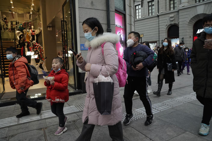 FILE - In this Jan. 14, 2021, file photo, residents, some wearing masks to protect themselves from the coronavirus, walk along a street in Wuhan in central China's Hubei province. One year after Wuhan's lockdown to curb the coronavirus, the Chinese city has long since sprung back to life. (AP Photo/Ng Han Guan, File)
