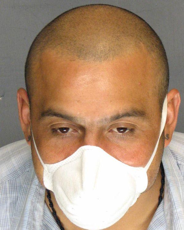 In this undated photo supplied by the San Joaquin County District Attorney's office, Armando Rodriguez is seen wearing a protective mask.  Prosecutors say 34-year-old Armando Rodriguez, a tuberculosis patient, has been arrested for refusing to take his medication and missing doctor appointments, and is endangering public health by not treating the airborne disease. (AP Photo/San Joaquin County District Attorney's Office)