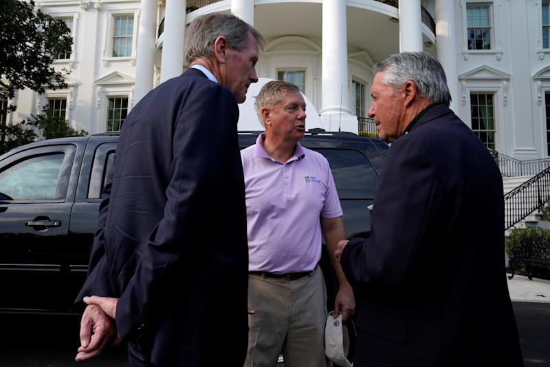 Sen. Lindsey Graham (center) and Gary Player return to the White House after a round of golf with the president. (Reuters)