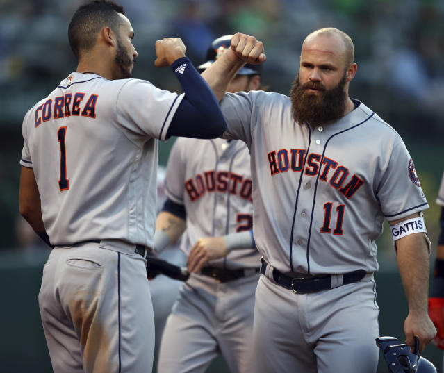 Houston Astros' Evan Gattis, right, celebrates with Carlos Correa (1) after hitting a three-run home run off Oakland Athletics' Emilio Pagan during the second inning of a baseball game Wednesday, June 13, 2018, in Oakland, Calif. (AP Photo/Ben Margot)