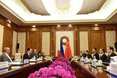 Philippine Foreign Affairs Secretary Alan Peter Cayetano, second from left, talks with Chinese Foreign Minster and State Counselor Wang Yi, second from right, during their meeting at the Diaoyutai State Guesthouse in Beijing, China March 21, 2018. Parker Song/Pool via REUTERS