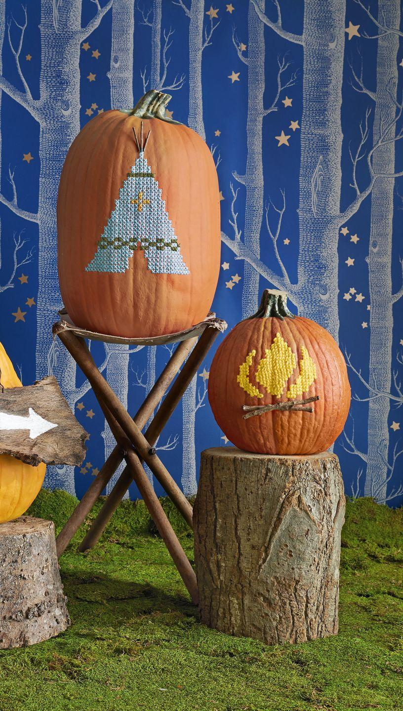 """<p>Add homespun charm to your decor with our tent and campfire. <strong><br></strong></p><p><strong>Make the pumpkins</strong>: Download and print our <a href=""""http://clv.h-cdn.co/assets/cm/15/31/PumpkinTemplates.pdf"""" rel=""""nofollow noopener"""" target=""""_blank"""" data-ylk=""""slk:cross-stitch patterns"""" class=""""link rapid-noclick-resp"""">cross-stitch patterns</a>. (Adjust pattern size as needed.) Tape onto artificial, carvable pumpkins. (Trust us: You'll want to display these year after year.) Punch through the pattern's cross-stitch points with an awl. Use a jab saw to cut an opening in the bottom of both pumpkins large enough for your hand to work inside. Cross-stitch using a tapestry needle and yarn. For tent support poles and campfire logs, adhere twigs with hot-glue.</p>"""