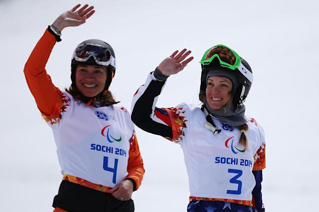 SOCHI, RUSSIA - MARCH 14: Gold medalist Bibian Mentel-Spee (L) of the Netherlands and bronze medalist Amy Purdy of the United States celebrate during the flower ceremony for the Women's Para Snowboard Cross Standing on day seven of the Sochi 2014 Paralympic Winter Games at Rosa Khutor Alpine Center on March 14, 2014 in Sochi, Russia. (Photo by Hannah Peters/Getty Images)