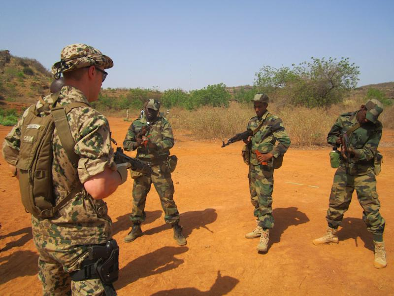 In this photo taken Monday, April 8, 2013, a Swedish instructor watches as Malian soldiers practice arming their weapons, during a European Union training session in the village of Koulikoro, 60 kilometers (37 miles) outside Bamako, Mali. In preparation for the final pullout of French troops from Mali, a European Union team has started training Malian soldiers for battle against jihadists who overran much of this west African country before they were pushed back by a French military intervention. (AP Photo/Baba Ahmed)