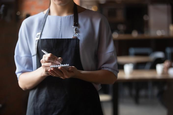 Close up attractive waitress wearing black apron standing in cozy coffeehouse, female cafe worker with notebook in hands waiting for, ready to take customers, guests order in restaurant