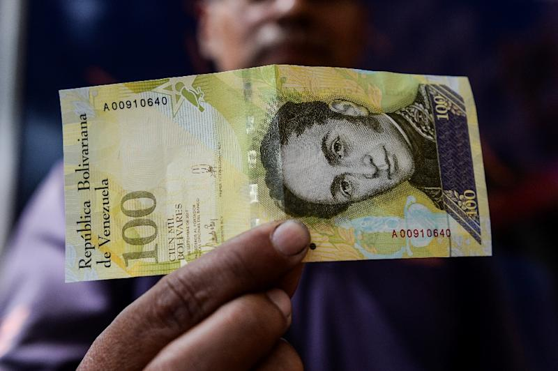 A man shows a new one hundred thousand-Bolivar-note in Caracas worth 29.89 US dollars in the official market and 2 dollars in the black market at November 9, 2017 exchange rate