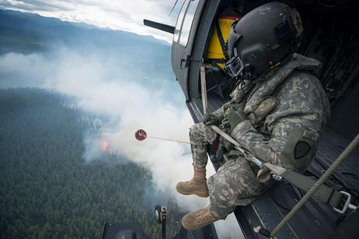 View of a burning forest from a helicopter with a soldier sitting in the open helicopter door