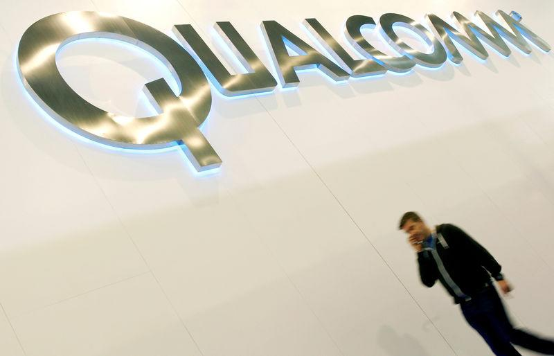 FILE PHOTO: A man walks past a Qualcomm advertising logo at the Mobile World Congress at Barcelona