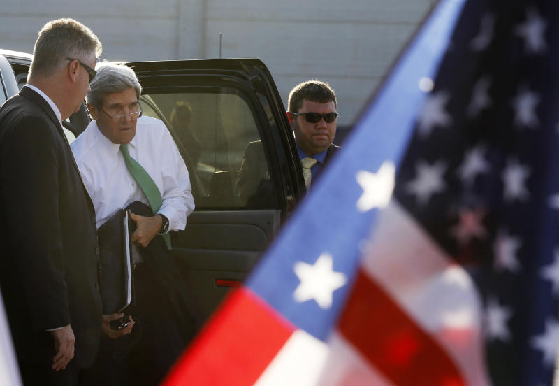 U.S. Secretary of State John Kerry, in white, gets out of his car before departing Ben Gurion airport in Tel Aviv, Israel, Sunday, Sept. 15, 2013. Kerry on Sunday sent a strong warning to Syria, saying 'the threat of force is real' if it does not carry out an internationally brokered agreement to hand over its chemical weapons. (AP Photo/Larry Downing, Pool)