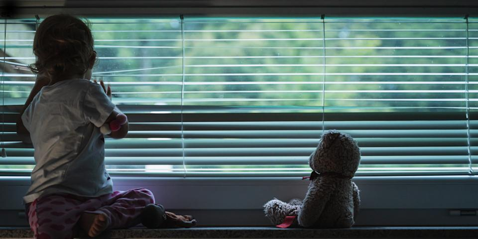 Toddler girl looking out the window through blinds.