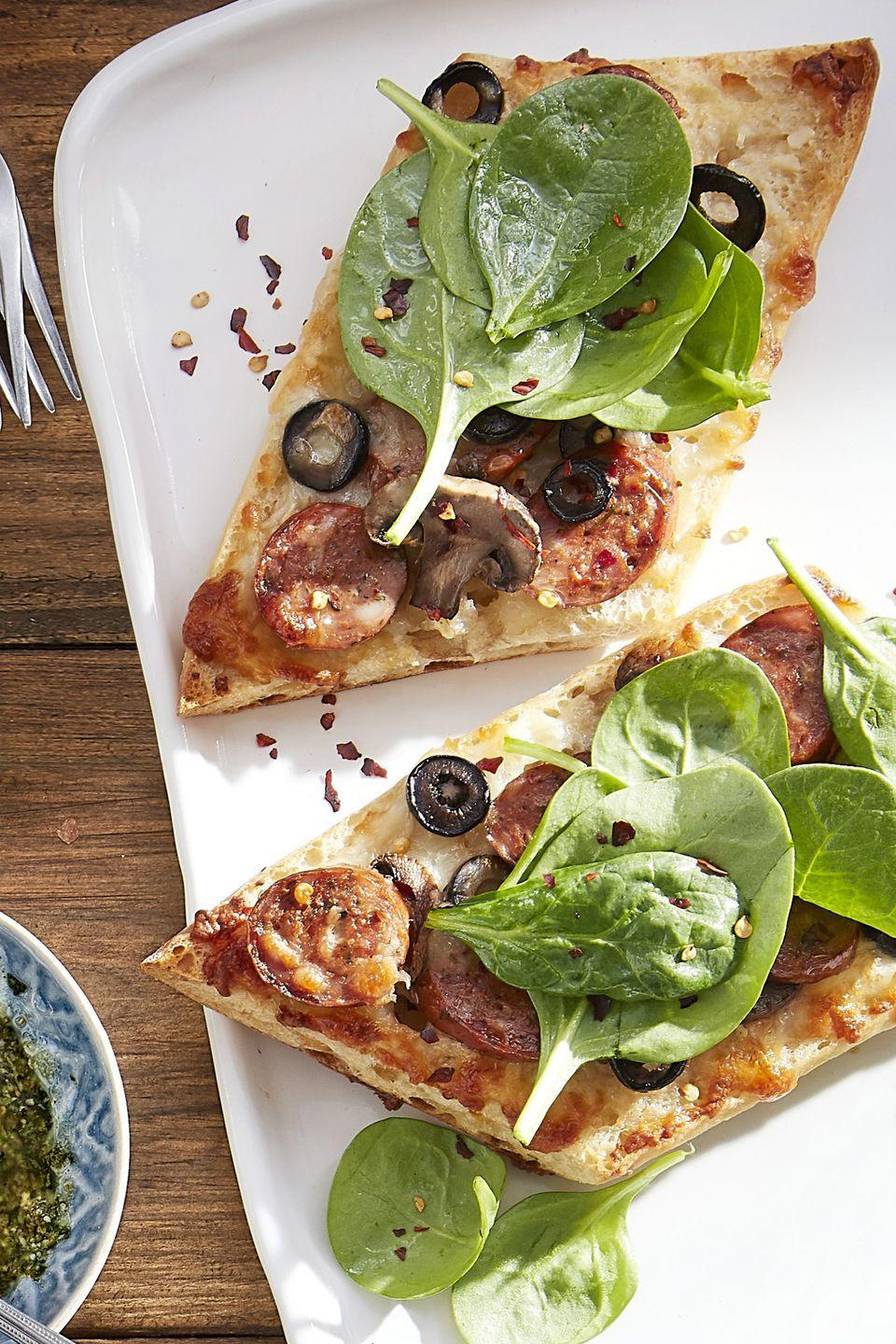 """<p>Chicken sausage, olives, and spinach are about to become your new favorite pizza toppings.</p><p><strong><a href=""""https://www.countryliving.com/food-drinks/recipes/a44232/sausage-mushroom-black-olive-white-pizzas-recipe/"""" rel=""""nofollow noopener"""" target=""""_blank"""" data-ylk=""""slk:Get the recipe"""" class=""""link rapid-noclick-resp"""">Get the recipe</a>.</strong> </p>"""